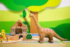 Δεινόσαυρος παιχνιδιών που εξετάζει μια γέφυρα και τα σπίτια άνωθεν Στοκ Φωτογραφία