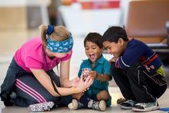 ΔΕΛΧΙ, ΙΝΔΙΑ - 25 ΜΑΡΤΊΟΥ 2013: Ινδικά παιδιά ευτυχή βλέποντας τη φωτογραφία τους στο smartphone του τουρίστα Στοκ Εικόνα