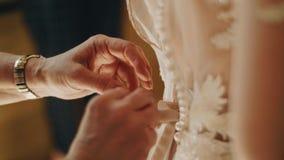Δεμένα χέρια κορδόνια γυναικών σε ένα φόρεμα των λευκών γυναικών Χέρια κινηματογραφήσεων σε πρώτο πλάνο Αμοιβές γυναικών απόθεμα βίντεο