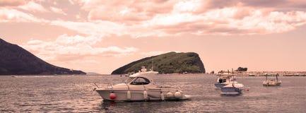 : Δεμένα motorboats ενάντια στο νησί Άγιου Βασίλη υποβάθρου στην αυγή Στοκ Εικόνες