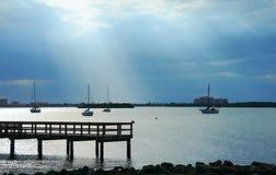 Δεμένα sailboats στον ήρεμο κόλπο με τις δραματικές ακτίνες ήλιων σύννεφων Στοκ Εικόνα