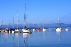 Δεμένες πλέοντας βάρκες στο μπλε ήρεμο νερό Στοκ φωτογραφία με δικαίωμα ελεύθερης χρήσης