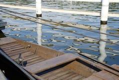 Δεμένο αγροτικό ξύλινο αλιευτικό σκάφος στον ποταμό με την αντανάκλαση της άσπρης αποβάθρας Στοκ Φωτογραφίες