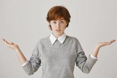 Δεν έχω καμία ιδέα για ποιο πράγμα μιλάτε Μπερδεμένος και ανίδεος redhead υπάλληλος που στέκεται με τους φοίνικες και Στοκ φωτογραφία με δικαίωμα ελεύθερης χρήσης