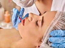 Δερμικά χείλια υλικών πληρώσεως της γυναίκας στο σαλόνι SPA με το beautician στοκ εικόνες