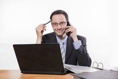 Δεσμευμένος υπάλληλος με τα γυαλιά που χαμογελά στο τηλέφωνο Στοκ Εικόνες