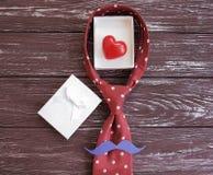 δεσμός, καρδιά, εορταστικός δημιουργικός κιβωτίων δώρων mustache σε ένα ξύλινο υπόβαθρο Στοκ Εικόνες