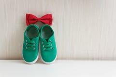 Δεσμός τόξων και πράσινα παπούτσια στον τοίχο υποβάθρου με την ταπετσαρία Στοκ Εικόνα