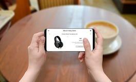 Δευτέρα Syber και μαύρες διαπραγματεύσεις Παρασκευής on-line Κινητό τηλέφωνο χρήσης γυναικών στην αναζήτηση της πώλησης Στοκ φωτογραφία με δικαίωμα ελεύθερης χρήσης