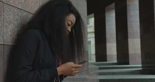 Δευτερεύοντα ακουστικά Texting μουσικής ακούσματος κοριτσιών πορτρέτου νέα όμορφα γοητευτικά αφρικανικά που κουβεντιάζουν κινητό  απόθεμα βίντεο