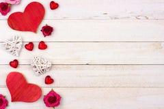 Δευτερεύοντα σύνορα ημέρας βαλεντίνων των καρδιών, των λουλουδιών και του ντεκόρ ενάντια στο άσπρο ξύλο στοκ εικόνα