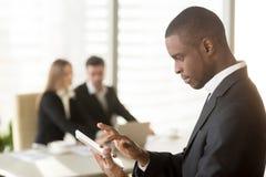 Δευτερεύον πορτρέτο του αμερικανικού smartphone εκμετάλλευσης επιχειρηματιών afro ή Στοκ Εικόνες