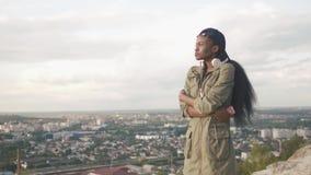Δευτερεύον πορτρέτο του ελκυστικού νέου αφρικανικού κοριτσιού που χαλαρώνει και που απολαμβάνει τη θέα πόλεων πανοράματος 4K φιλμ μικρού μήκους