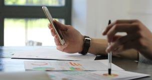 Δευτερεύουσα κινηματογράφηση σε πρώτο πλάνο του γραφείου συνεδρίασης επιχειρησιακών ατόμων, που χρησιμοποιεί το smartphone του, α απόθεμα βίντεο