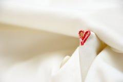 Δευτερεύουσα κόκκινη μορφή haert με buttonhole τη βελονιά και το άσπρο febric υπόβαθρο Στοκ εικόνα με δικαίωμα ελεύθερης χρήσης