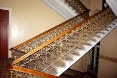 Δευτερεύουσα σκάλα στο κτήριο με τα ξύλινα κιγκλιδώματα και τη σφυρηλατημένη περίφραξη Στοκ Εικόνες
