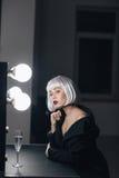 Δελεαστική ξανθή σαμπάνια κατανάλωσης γυναικών στο βεστιάριο στοκ φωτογραφία με δικαίωμα ελεύθερης χρήσης