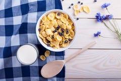 Δημητριακά με το μύρτιλλο, το φλυτζάνι γάλακτος, το λουλούδι και το κουτάλι Στοκ Φωτογραφία