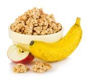 Δημητριακά προγευμάτων με την κινηματογράφηση σε πρώτο πλάνο μπανανών και μήλων στο άσπρο υπόβαθρο Στοκ Εικόνες