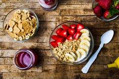 Δημητριακά προγευμάτων με την μπανάνα και τη φράουλα στα κύπελλα Στοκ Φωτογραφίες