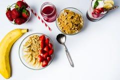 Δημητριακά προγευμάτων με την μπανάνα και τη φράουλα στα κύπελλα Στοκ εικόνα με δικαίωμα ελεύθερης χρήσης