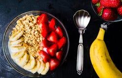 Δημητριακά προγευμάτων με την μπανάνα και τη φράουλα στα κύπελλα Στοκ Εικόνες