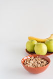 Δημητριακά στο κύπελλο με τα φρέσκα μήλα, μπανάνες στο άσπρο υπόβαθρο Στοκ εικόνες με δικαίωμα ελεύθερης χρήσης