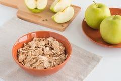 Δημητριακά στο κύπελλο, το φρέσκες σύνολο μήλων και και την περικοπή στα κομμάτια στον ξύλινο πίνακα Στοκ εικόνες με δικαίωμα ελεύθερης χρήσης