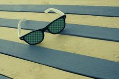 Δημιουργικά γυαλιά ηλίου σε μια ριγωτή επιφάνεια Στοκ Φωτογραφίες