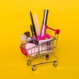 Δημιουργική έννοια με το καροτσάκι αγορών με το makeup σε ένα κίτρινο υπόβαθρο Στοκ Εικόνες