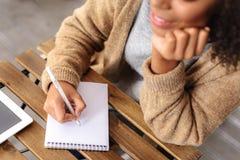 Δημιουργική λήψη κοριτσιών σημειώσεις στο σημειωματάριο Στοκ Εικόνες