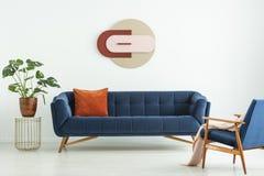 Δημιουργική γεωμετρική τέχνη σε έναν άσπρο τοίχο επάνω από έναν κομψό μπλε καναπέ σε ένα mid-century σύγχρονο εσωτερικό καθιστικώ στοκ εικόνα