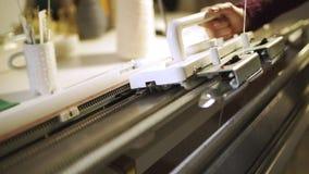 Δημιουργική γυναίκα που κάνει την πλεκτή σύσταση στην υφαίνοντας μηχανή στο εργαστήριο φιλμ μικρού μήκους