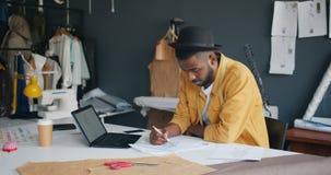 Δημιουργική εικόνα σχεδίων ραφτών των νέων ενδυμάτων που εξετάζουν την οθόνη lap-top απόθεμα βίντεο