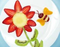 Δημιουργική μέλισσα επιδορπίων παιδιών φρούτων στη μορφή λουλουδιών Στοκ φωτογραφία με δικαίωμα ελεύθερης χρήσης