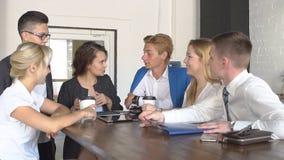Δημιουργική νέα ομάδα που πίνει μαζί τον καφέ που κρατά μια ταμπλέτα που συζητά μια επιχείρηση σπιτιών καφέ ομαδικής εργασίας προ φιλμ μικρού μήκους