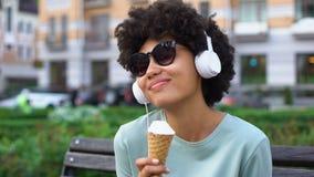 Δημιουργική ξένοιαστη γυναίκα που απολαμβάνει τη μουσική στα ακουστικά, που τρώνε το παγωτό στον πάγκο απόθεμα βίντεο