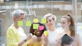 Δημιουργική ομάδα γοητείας που γράφει στις αυτοκόλλητες ετικέττες στον τοίχο γυαλιού γραφείων απόθεμα βίντεο