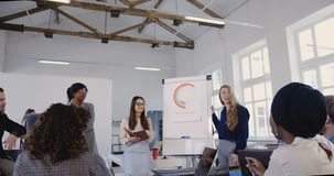Δημιουργική ομάδα γραφείων Multiethnic που ακούει το ευτυχές ξανθό σεμινάριο χρηματοδότησης επιχειρησιακών γυναικών οδηγώντας η σ φιλμ μικρού μήκους