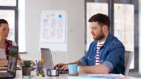 Δημιουργική ομάδα με τα lap-top που λειτουργούν στο γραφείο απόθεμα βίντεο