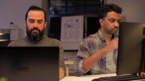 Δημιουργική ομάδα με τον υπολογιστή που λειτουργεί αργά στο γραφείο απόθεμα βίντεο