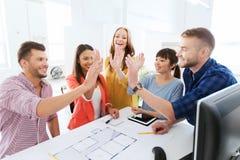 Δημιουργική ομάδα που κάνει υψηλά πέντε στο γραφείο στοκ φωτογραφίες