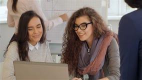 Δημιουργική ομάδα της εργασίας τεσσάρων γυναικών ενεργά στο γραφείο απόθεμα βίντεο