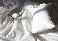 Δημιουργική σύνθεση φωτογραφιών με το βιβλίο και το άσπρο κρεβάτι κάτω από το φως ήλιων από το παράθυρο στοκ εικόνα