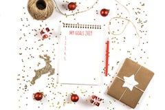 Δημιουργική σύνθεση Χριστουγέννων με το σημειωματάριο και τις διακοσμήσεις στοκ εικόνα