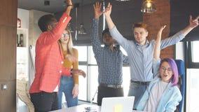Δημιουργικοί νέοι που επιδοκιμάζουν στον ομιλητή στο σύγχρονο γραφείο απόθεμα βίντεο