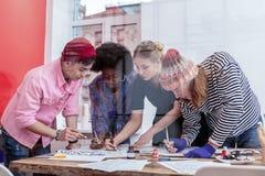 Δημιουργικοί σπουδαστές των βουρτσών και των μολυβιών ζωγραφικής σχολικής εκμετάλλευσης τέχνης στοκ εικόνα