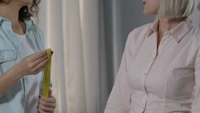 Δημιουργικός εργαζόμενος ατελιέ που κάνει τα μέτρα του γυναικείου πελάτη για τη διαταγή επιχειρησιακών κοστουμιών απόθεμα βίντεο
