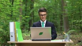 Δημιουργικός νέος διευθυντής που εργάζεται στο πρόγραμμα στο όμορφο πάρκο, γραφείο στη φύση φιλμ μικρού μήκους