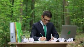 Δημιουργικός νέος επιχειρηματίας που γράφει κάτω τις καλές ιδέες στο γραφείο στο πράσινο δάσος φιλμ μικρού μήκους
